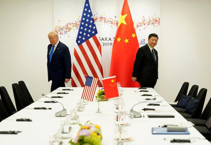 2019年6月美國總統川普(左)與中國大陸國家主席習近平在日本大阪的G20峰會碰面,兩人分別走向雙邊會談的坐位。(圖/路透)