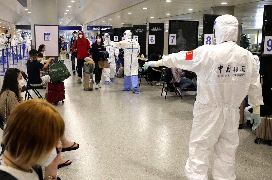 圖為上海浦東國際機場海關人員引導入境旅客進行登記檢查。新華社