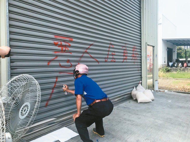 一名男子氣不過,拿紅漆在廠房鐵門噴字洩憤。記者徐白櫻/攝影