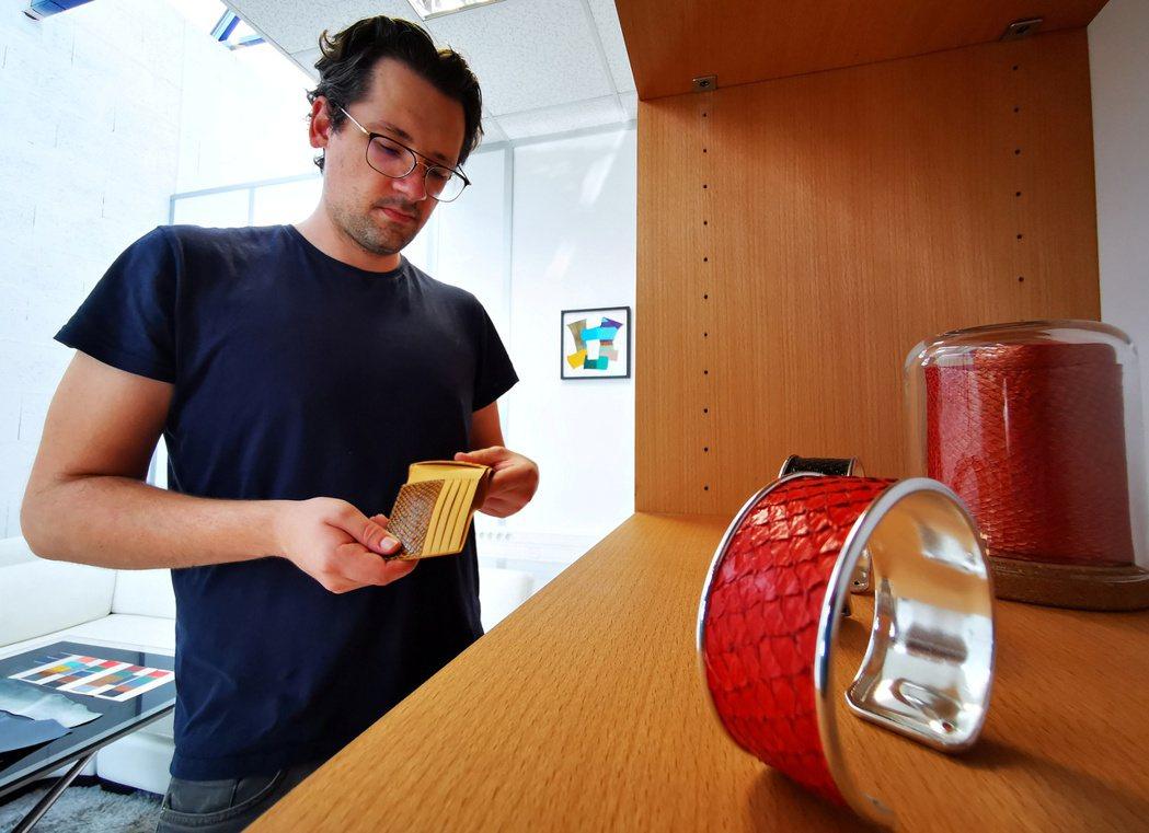 Ictyos共同創辦人馬拉蒂安正檢視用鮭魚皮做成的皮夾。(路透)