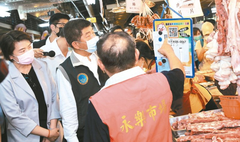 台北市副市長黃珊珊(左)與衛福部長陳時中(左二)到迪化商圈推動豬肉標示,在永樂市場一家豬肉攤,看著標示產地的QR Code。 記者潘俊宏/攝影