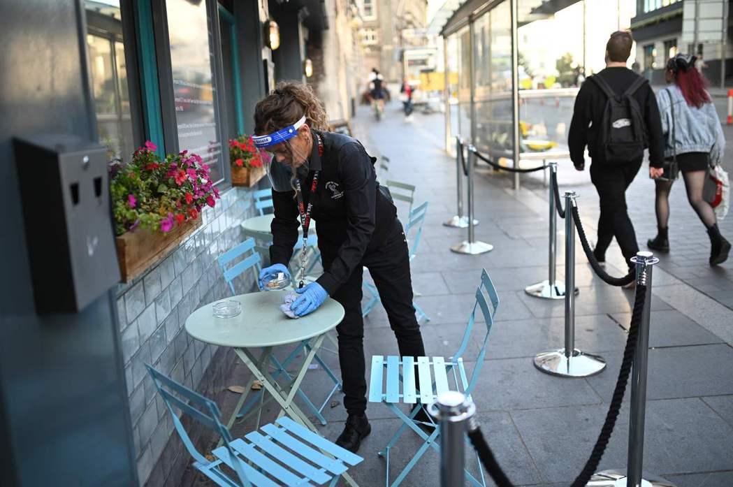 英國利物浦一名女服務員18日穿著防護設備清理餐桌。法新社