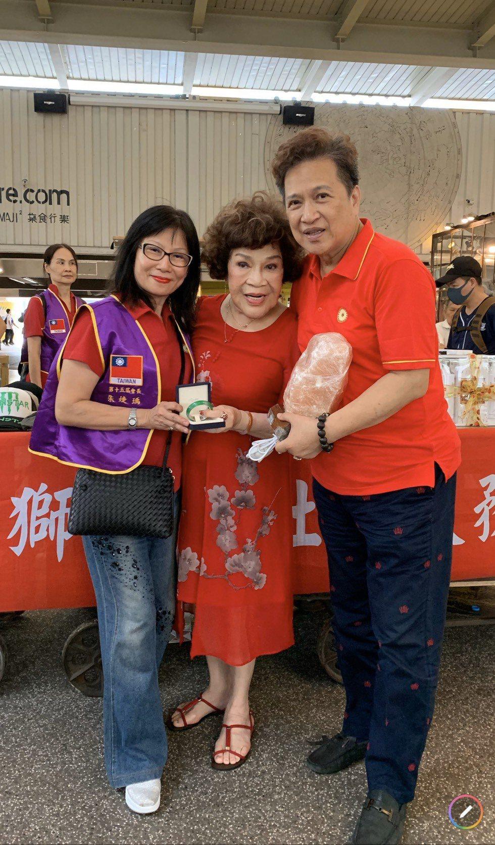 李朝永(右起)、阿姑周遊、台北市獅子會會長朱婕瑀為籌募救助車,捐出手鐲、鹽燈義賣