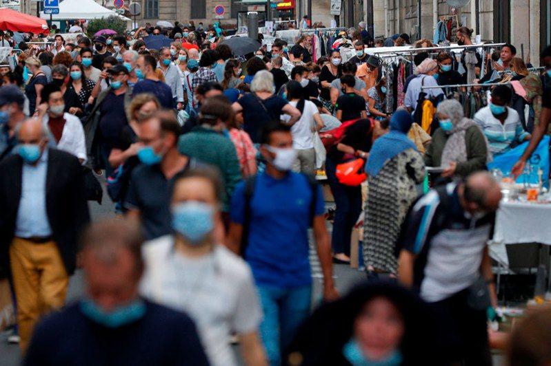 法國當局19日通報,境內過去24小時新增1萬3498人確診感染新冠肺炎,再創疫情爆發以來單日新高紀錄。圖為巴黎市中心的一處跳蚤市場裡戴著防護口罩的群眾。