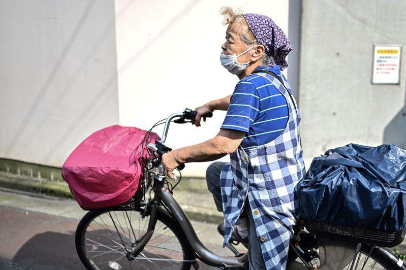 日本一名戴口罩的年長婦女今年七月騎單車經過東京街頭。(法新社)
