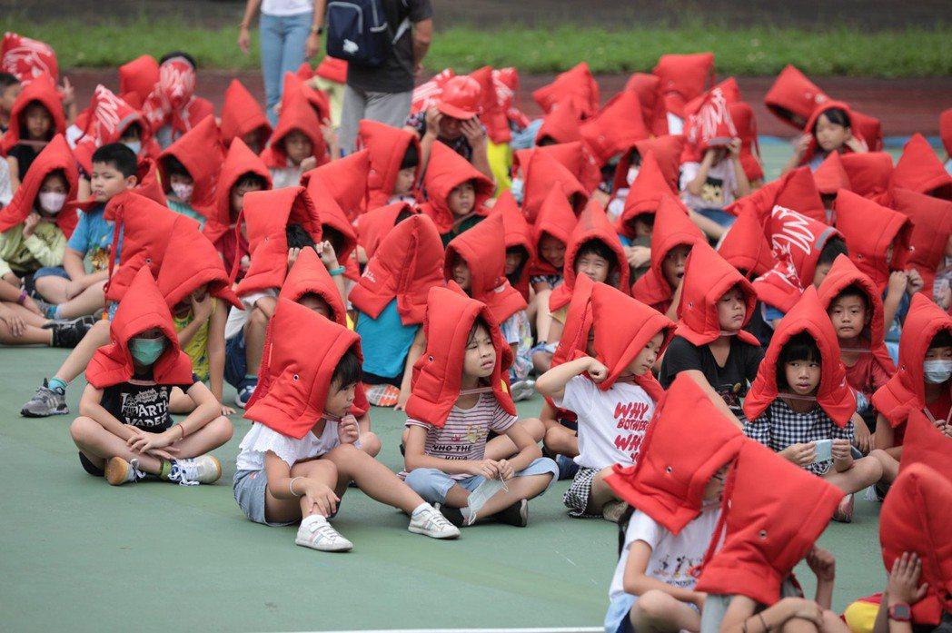 921國家防災日,基隆市碇內國小學童戴上防災頭套進行避難演練。 圖/基隆市教育局提供