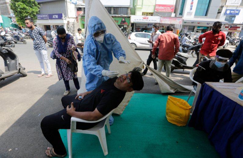 印度染疫死亡總數8萬8935人。確診病例總數達560萬人。圖為印度當地醫療人員正為民眾採檢。 美聯社