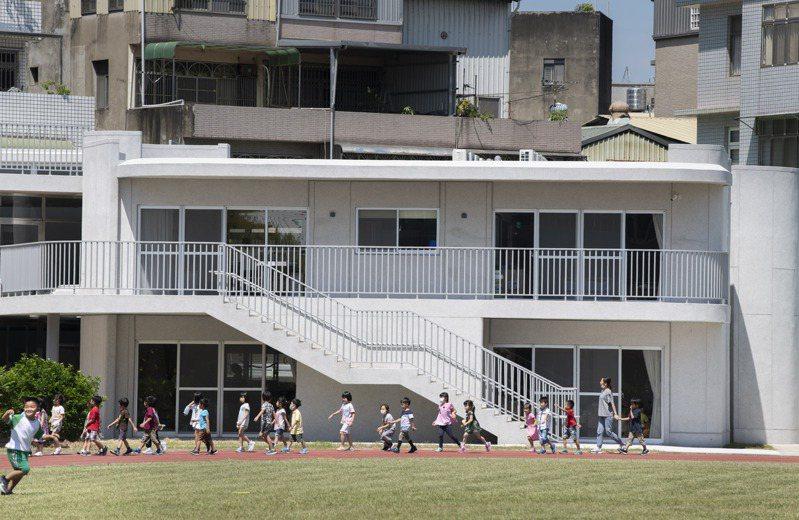 林智堅表示,三民附幼每間教室都有前後落地窗,還有寬敞的半戶外空間與露台,圓弧狀建築為灰白色調,讓空間得以延伸。圖/新竹市政府提供