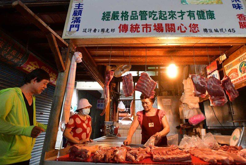 天剛亮,傳統市場肉攤擺上新鮮溫體豬肉,供民眾採買。「冰過的不好吃,」有溫度才有鮮度,台灣人吃下去的七成豬肉都來自於此。圖片來源:劉國泰攝