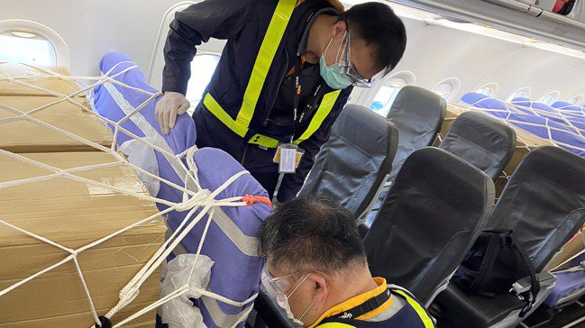 疫情期間,航空公司客機臨時拿來充當貨機使用,工作人員把貨物安置在客艙中。 圖/歐...