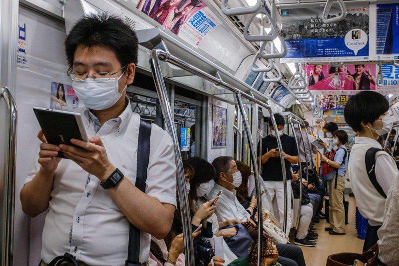 日本通勤族今年七月搭乘東京地鐵時紛紛戴上口罩防疫。 法新社