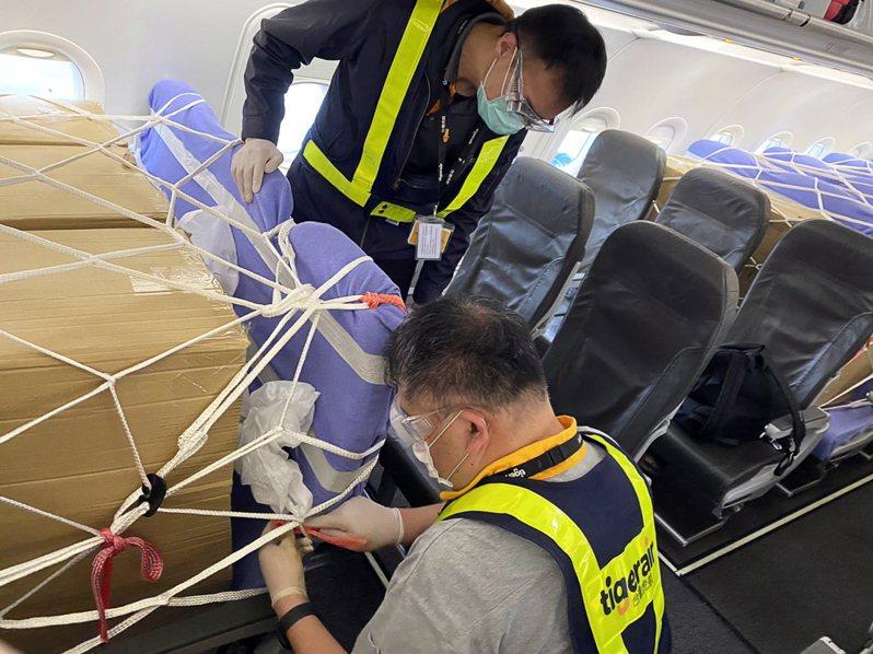 疫情期間,航空公司客機臨時拿來充當貨機使用,工作人員把貨物安置在客艙中。(歐新社)