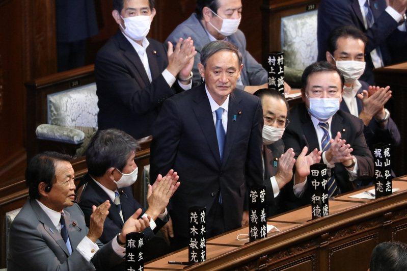 新當選的日本第99任首相、自民黨總裁菅義偉(中)。 新華社