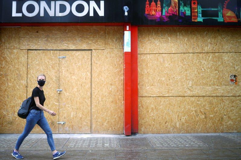 圖為英國倫敦民眾戴口罩行經街頭。路透