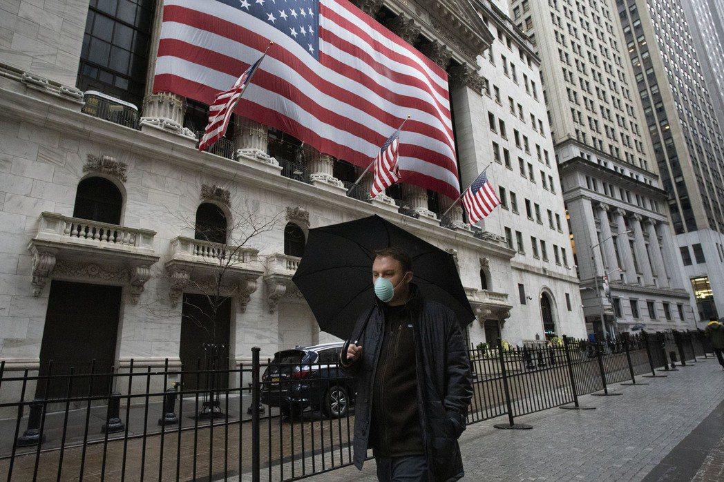 一名戴著口罩的男子走過華爾街上的紐約證券交易所。(圖/美聯社)