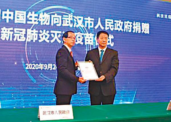 楊曉明(右)代表中國生物向武漢市捐贈10萬人份新冠肺炎滅活疫苗。(香港文匯網)