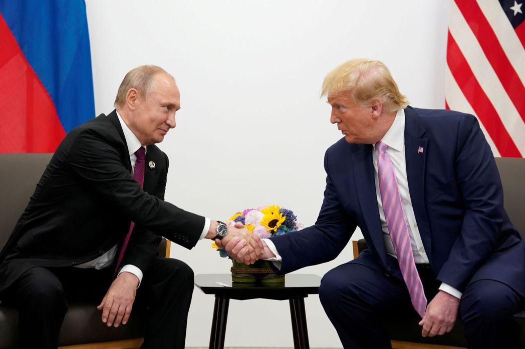 俄羅斯總統普亭(左)在去年G20大阪峰會上與美國總統川普握手致意。路透