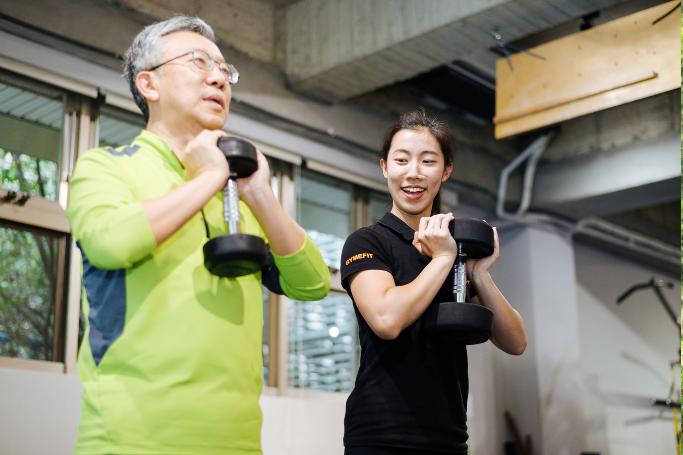 健身教練珍珍(右)陪伴患有五十肩的父親一起健身,改善父親舊疾。 記者陳軍杉/攝影