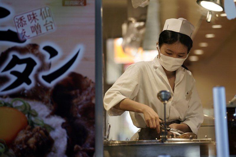 東京一家餐廳員工10日戴口罩為客人準備餐點。(美聯社)