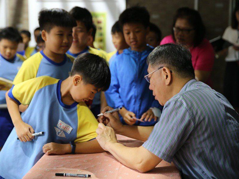 台北市長柯文哲(右一)昨天前往北市永建國小視察節能減碳永續校園成果,最後還幫學生簽名留念。記者季相儒/攝影