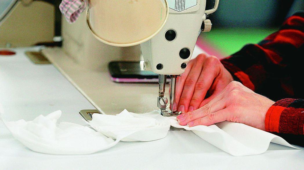 圖為一家成衣廠近日轉型生產醫用口罩。 (路透)