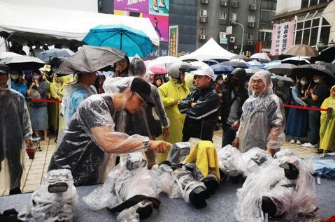 王心凌今天在西門町舉行「My! Cyndi!」精選輯簽簽唱會,天空下著不小的雨勢,但是熱情的粉絲仍穿著雨衣打著傘熱情冒雨相挺,媒體攝影也將相機包起雨衣拍攝。