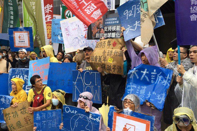 青年抗暖大遊行昨天登場,核四公投領銜人黃士修在合影人群中舉牌「支持核能抗暖化」,引發一陣尷尬。 記者吳姿賢/攝影