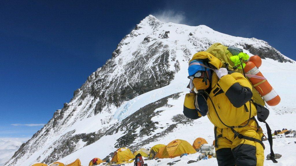 一名雪巴人在珠穆朗瑪峰揹運帳棚與物資上山。 圖/法新社