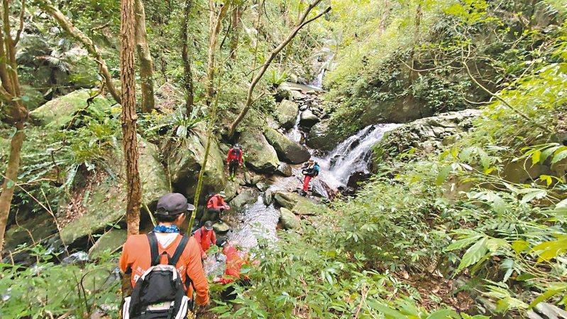 台灣高山林立,山谷陡峭難行,救難人員要綁上攀降繩索行進,山域搜救不輕鬆。圖/六龜飛鷹大隊提供