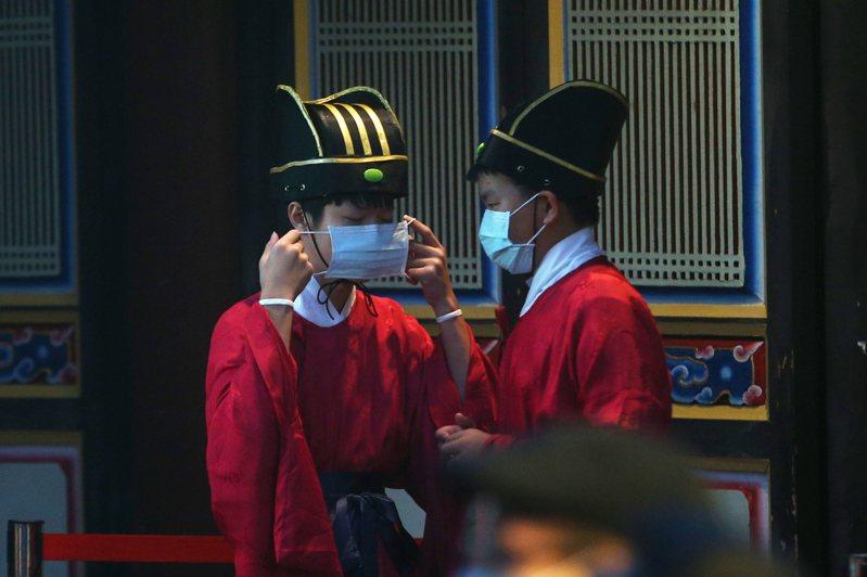 台北市祭孔大典上午在台北孔廟舉行,受到疫情影響,只開放150位民眾觀禮,人潮大幅減少。禮生在典禮開始前趕緊整理口罩。記者蘇健忠/攝影
