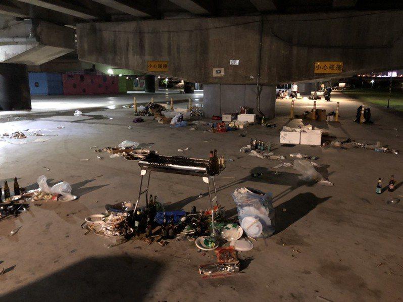有民眾在台北民權大橋下方發現疑似烤肉活動後還未收拾的「殘局」,不只廚餘垃圾未倒、酒瓶堆滿地,甚至連炭火都還沒滅就不見人的蹤影。圖擷自PTT