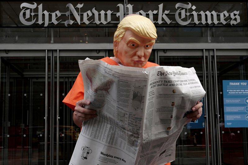 一名男子裝扮成充上橙色囚裝的川普總統,28日在紐約市曼哈頓的紐約時報大樓前,閱讀當天紐時的川普稅務問題。紐約時報表示完全是盡媒體監督之責。(美聯社)