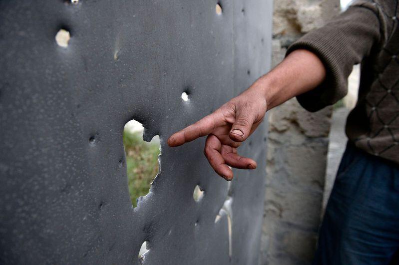 納哥諾卡拉巴克地區(Nagorny Karabakh)週末爆發激烈戰鬥,一名男子指出遭到砲擊的區域。法新社