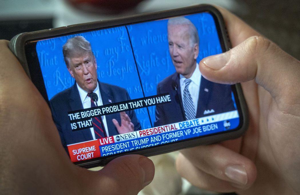 民眾用手機觀看美國總統大選首場電視辯論。歐新社