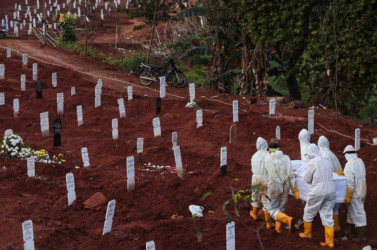 印度尼西亞雅加達一處墓園的工作人員穿著防護服搬運疑似新冠患者的棺槨。 新華社