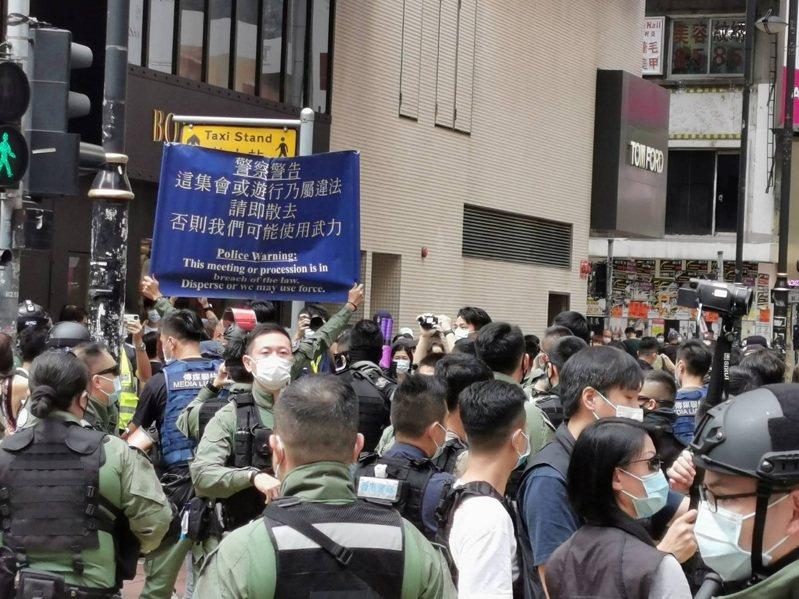 香港網友1日發起多區集會遊行,但至下午1時尚無大規模集結。銅鑼灣東角道一帶,有數百名防暴警察戒備,不時驅趕個別穿黑衣示威者。圖為防暴警察舉起藍旗,警告市民不要聚集。 中央社
