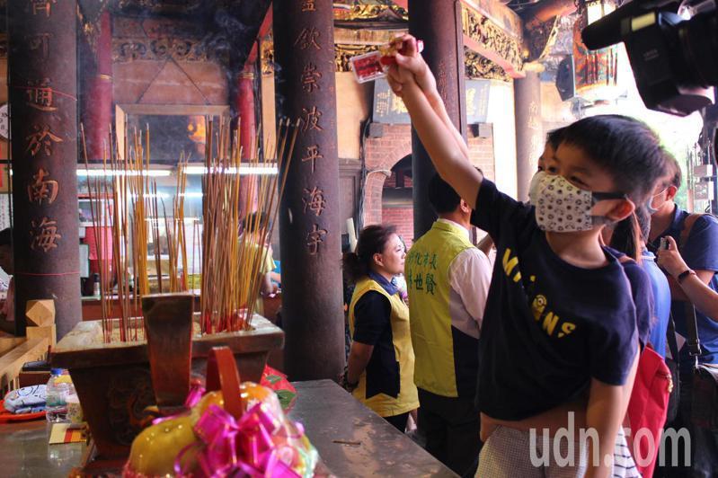 家長帶著孩子到南瑤宮向媽祖報名安。記者林敬家/攝影