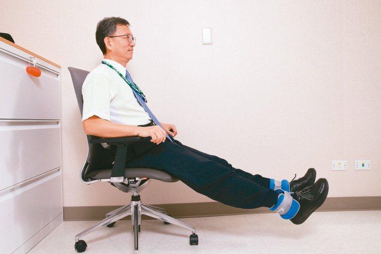 台大癌醫副院長王明鉅,在辦公室的時候,把腿平舉起來,鍛鍊腹肌。記者許正宏/攝影