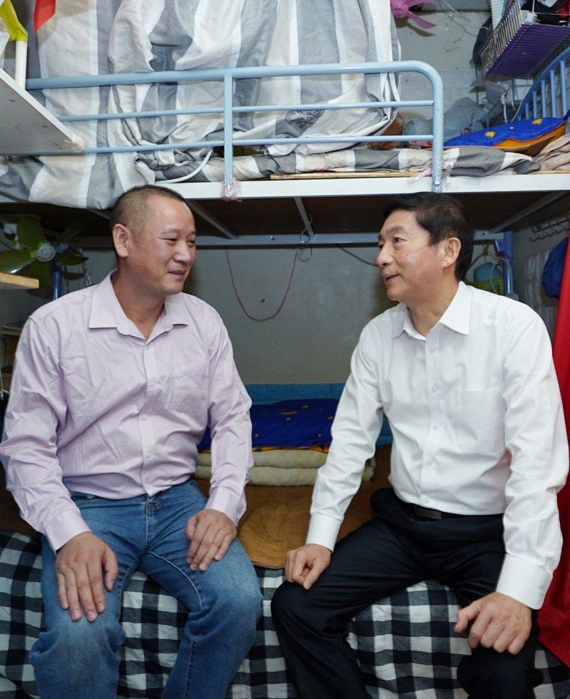 香港中聯辦主任駱惠寧(右)與住在香港九龍深水埗劏房的徐天民交談。(新華社)
