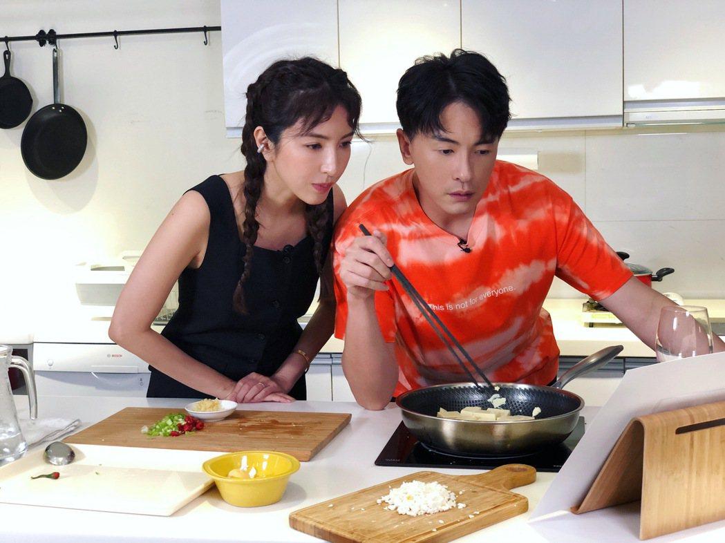 楊謹華(左)、鄭元暢看食譜步驟做菜。圖/M.I.E.最大國際娛樂提供