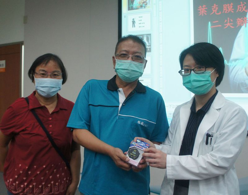 紀先生(中)感謝醫師吳詠斯(右)及台中榮總醫療團隊救命之恩,不但戒菸還樂當拒菸大使,吳詠斯贈送計步器加油鼓勵。圖/台中榮總提供