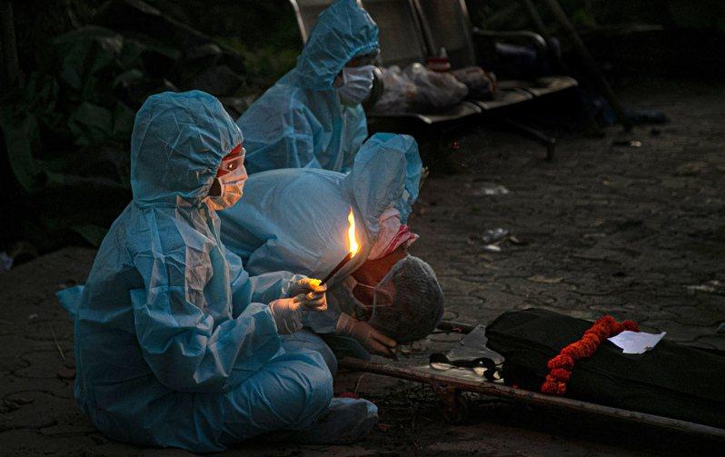 印度的新冠肺炎死亡人數3日累計破10萬人,圖為家屬穿著防護設備為亡者舉行葬禮儀式。(美聯社)
