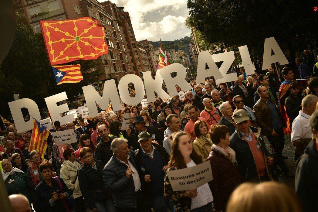 巴斯克首府畢爾包的獨派大示威。這些巴斯克示威者高舉著巴斯克語的「民主」字卡,並揮舞著西班牙北部三大獨派自治區——納瓦拉(紅底米字)、加泰隆尼亞(藍底白星)、巴斯克(紅綠配色)——各自的「國旗」。 圖/美聯社