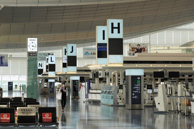 日本政府打算明年春季試辦開放外國觀光客入境。圖為日本東京羽田機場一名員工一日經過空蕩蕩的出境樓層。(歐新社)