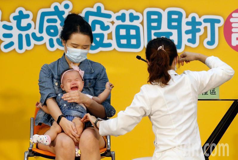 衛服部疾病管制署上午舉行「守護我們所愛的人」公費流感疫苗開打記者會,邀請一對父母帶著雙胞胎幼兒到現場接種,小女嬰打針後當場大哭。記者鄭超文/攝影