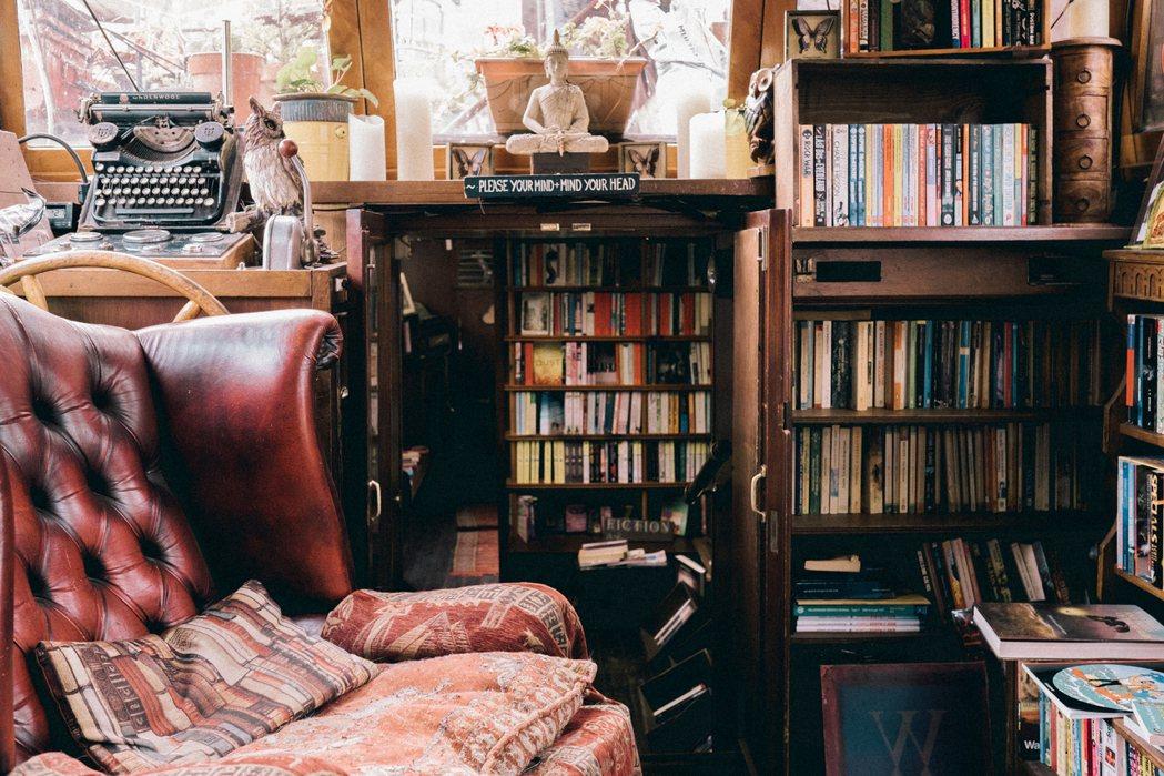 書店一隅,紅皮老沙發、復古毛毯、貓頭鷹木雕、古董打字機、佛像、二手書,件件老物構...