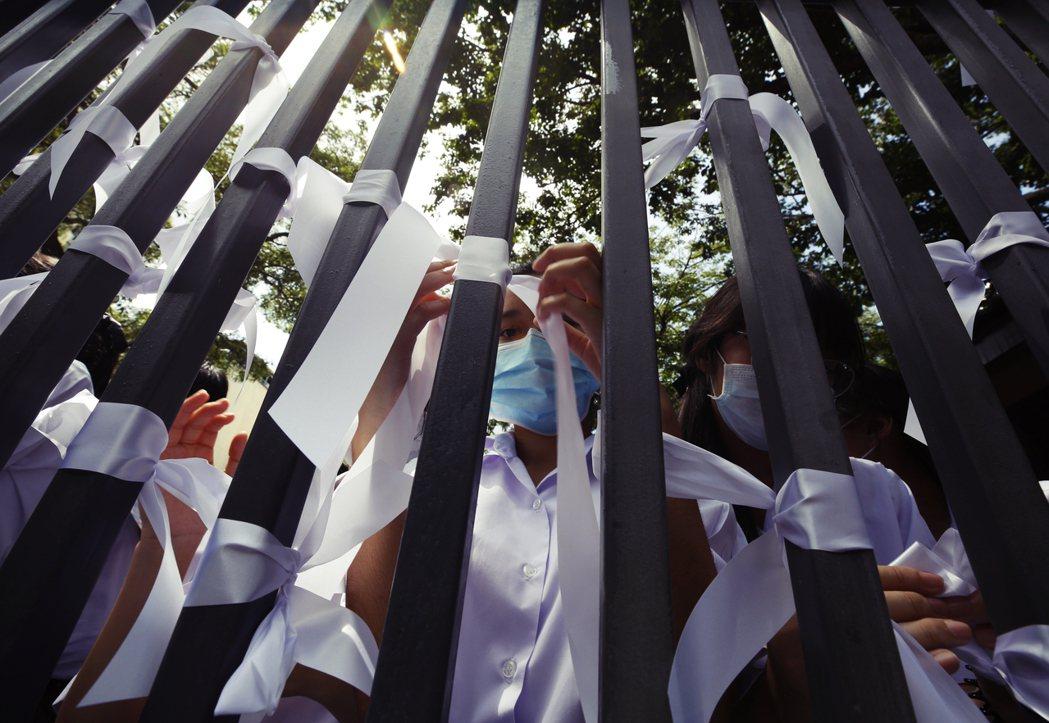 在泰國校園中,學生們在唱國歌時行起象徵反對專制的三指禮,繫上象徵反對暴力迫害的白...