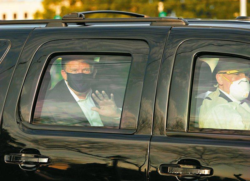 美國總統川普(左)四日搭車在馬里蘭州華特里德軍醫院外向支持者揮手。(法新社)