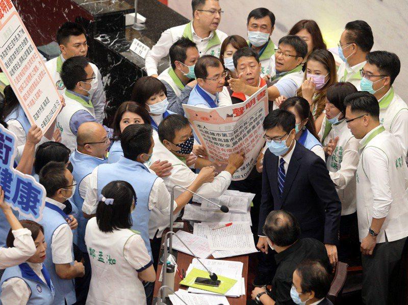 高雄市議會今天開議,國民黨團聯合質詢陳其邁,還要陳市長簽署拒絕美豬進口聲明書,被民進黨議員擋下,雙方一度推擠。記者劉學聖/攝影