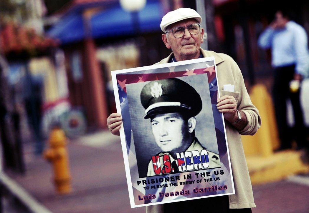 圖為邁阿密小哈瓦那,一名民眾舉著「恐怖分子」卡里萊斯的照片,上面寫著「美國英雄」...